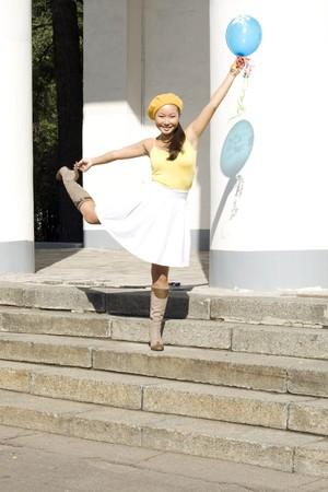 Girl dancing with baloon outdoor photo