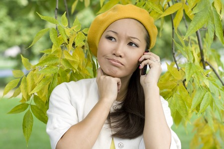 Girl talking by phone in autumn park photo