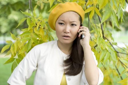 pensiveness: Ragazza parlare telefonicamente in autunno parco