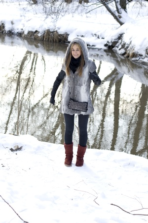 Smiling girl walking in winter forest photo