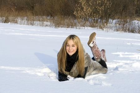 Happy girl lying in snow photo