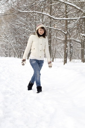 Beautiful girl walking in winter forest photo
