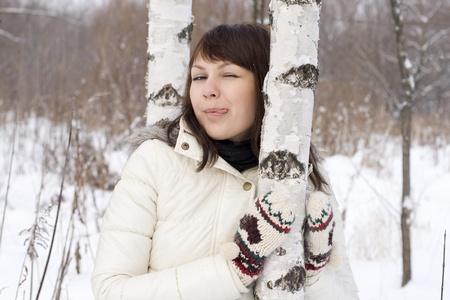 Cute girl walking in winter forest photo