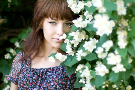 Closeup portrait of a beautiful girl standing among flowers photo