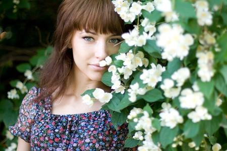Closeup portrait of a beautiful girl standing among flowers Stock Photo - 9952616