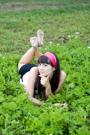 Pretty girl lying on grass photo