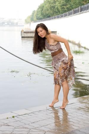 Beautiful girl walking near river photo