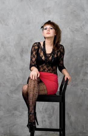 Cute gothic girl sitting on chair studio shot photo