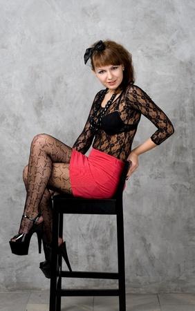 glam rock: Cute gothic girl sitting on chair studio shot