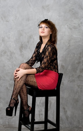 Cute gothic girl sitting on chair studio shot photo