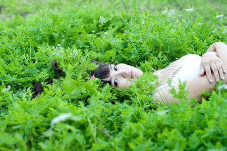 Closeup portrait of a beautiful girl lying among flowers photo