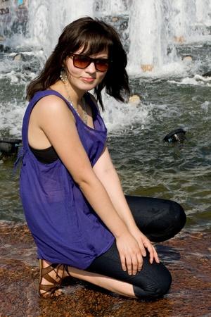 Girl walking near fountain in city photo