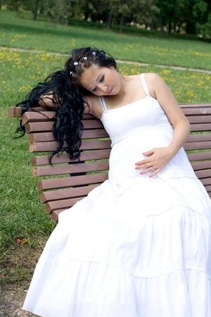 Beautiful pregnant girl walking in park photo