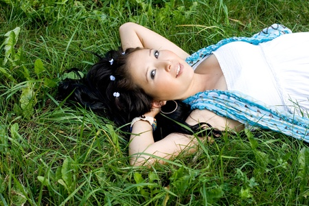 Beautiful pregnant girl lying on grass