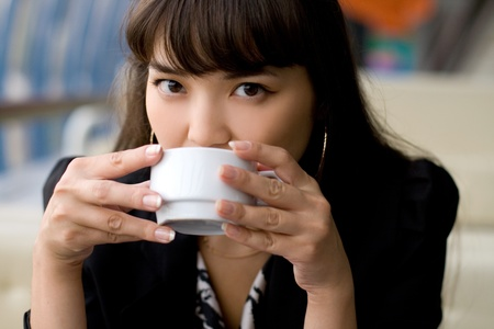 Businesswoman drinking tea in a cafe Stock Photo - 10423055