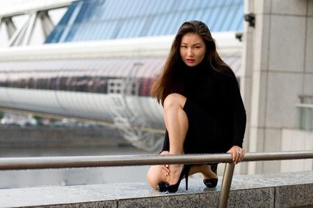 Sexy girl in black dress walking in city photo