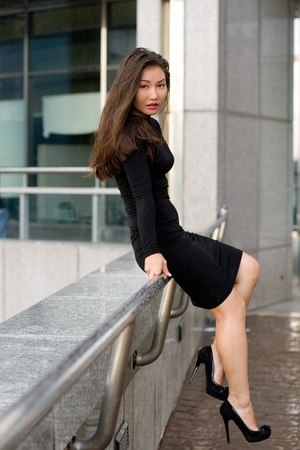 Sexy girl in black dress walking in city photo