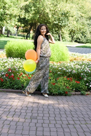 Joyful pregnant girl with colorful balloons walking in park photo