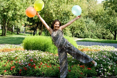Joyful pregnant girl with colorful balloons walking in park Stock Photo - 10609050