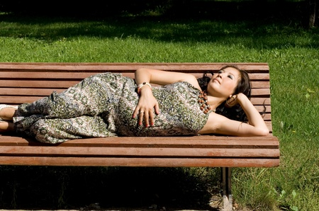 mother on bench: Beautiful pregnant girl lying on bench