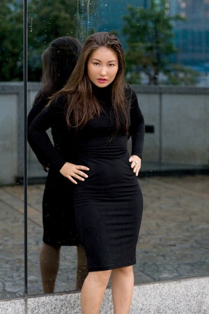 Sexy girl in black dress standing in front of a mirror