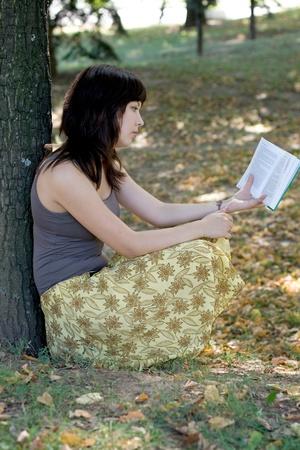 Girl reading book in park photo