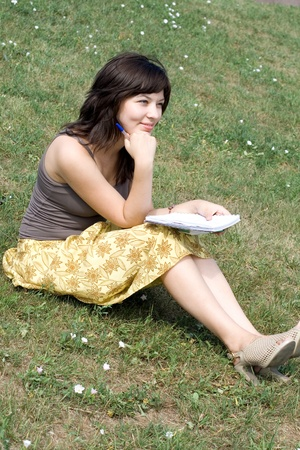 Girl sitting on grass in park photo