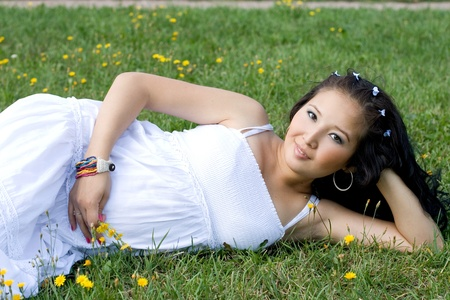 Beautiful pregnant girl lying on grass photo