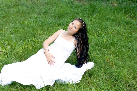 Beautiful pregnant girl sitting on grass photo