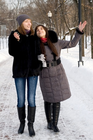 Two female friends walking in park in winter photo