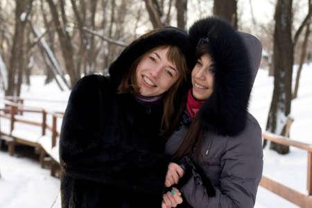 Two female friends walking in park in winter Stock Photo - 12499870