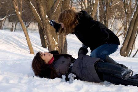 Two female friends walking in park in winter