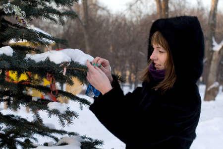 Girl decorating a fir tree photo