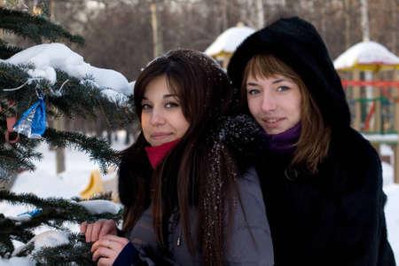 Two female friends walking in park in winter photo