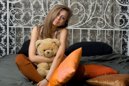 Pretty girl sitting on bed Stock Photo - 14434385