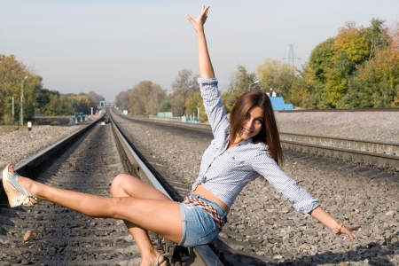 Beautiful girl sitting on rails photo