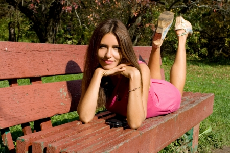 Girl lying on bench in autumn park