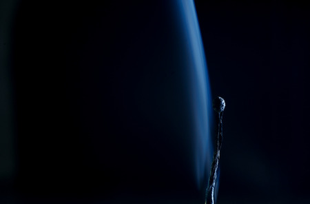Burnt match in a smoke on a black background