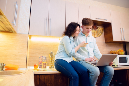 kitchen furniture: Young family sitting in kitchen with laptop Stock Photo