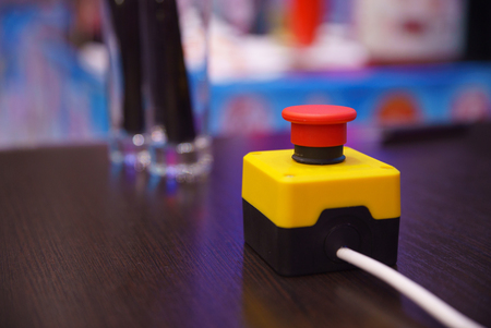 hysteria: Red button with a yellow stand on a dark table