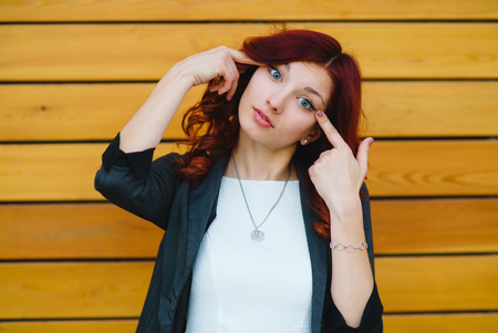 Girl with red hair makes a face with narrow eyes standing on a wooden background Stock Photo