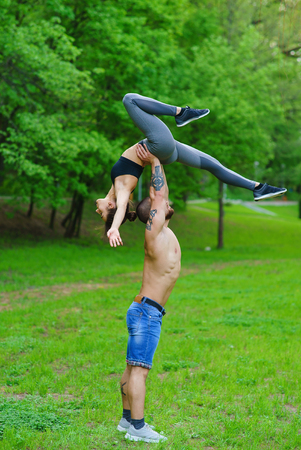 A guy and a girl are doing sports, aerial gymnastics in the park