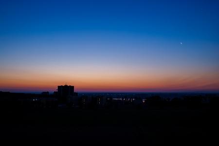 月が付いている都市の夜明け 写真素材