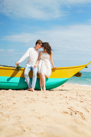 Couple in love of happy man and woman, travel. Beach wooden boat sand