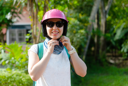A girl is zipping up a Asia travel helmet