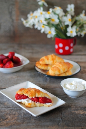Fresh baked croissants with whipped cream and strawberries photo