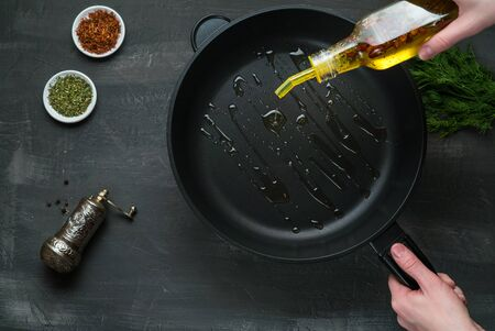 Man pouring cooking oil on the frying pan - Top View on a dark background
