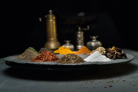 spices in variety on a dark background surrounded by oriental dishes space for text