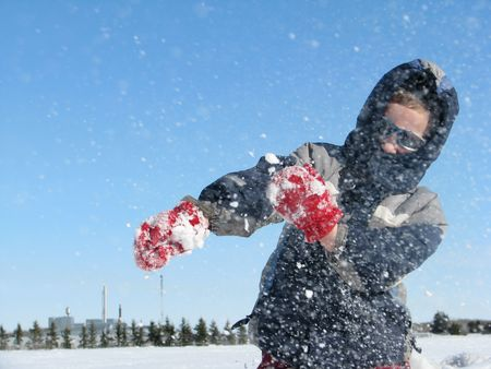 young child throws snow against blue sky Stock Photo