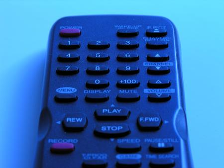 remote controls: Close Up Overview of Television Remote Control, Detail of Buttons and Command Controls of Remote Control Still Life in Blue Light on Plain Background